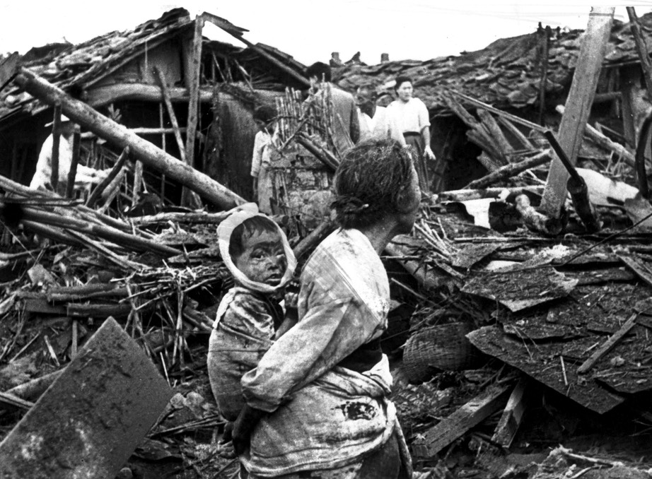An elderly woman and her grandchild wander among the debris of their wrecked home in the aftermath of an air raid by U.S. planes over Pyongyang, the Communist capital of North Korea, circa 1950. Photo- Keystone:Getty Images