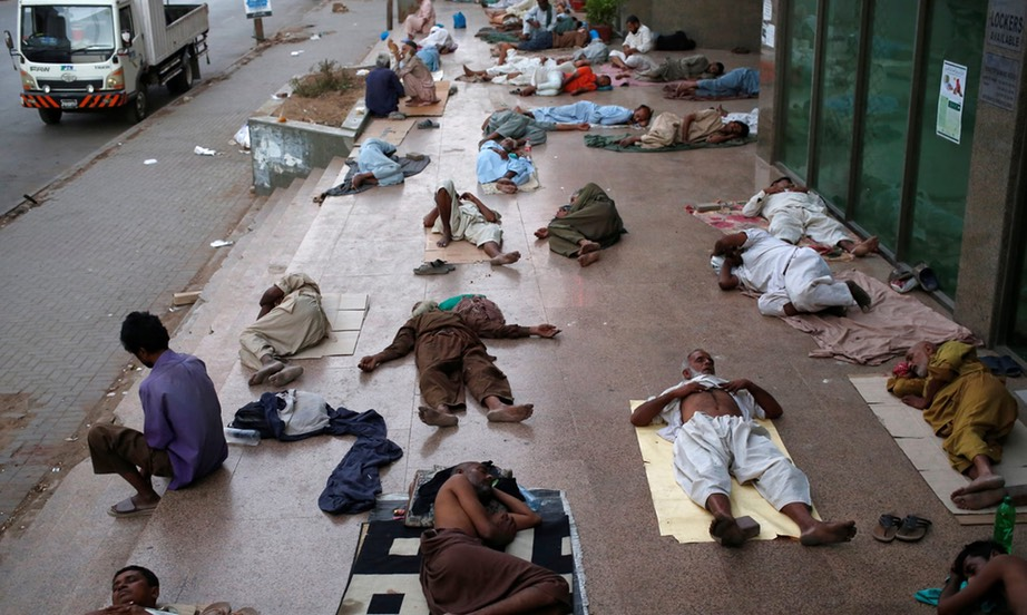 Residents sleep on the pavement in Karachi to escape the heat and frequent power outages. -Akhtar Soomro:Reuters